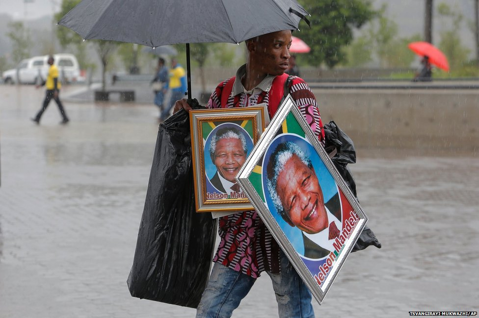 A man sells portraits of Nelson Mandela outside of the memorial service
