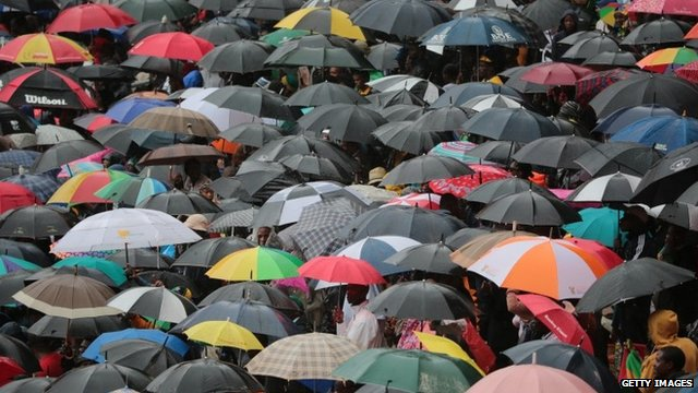 People take cover from the rain under umbrellas as they stand for the official memorial service for former South African President Nelson Mandela at the FNB Stadium