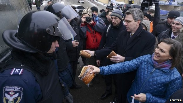 US Assistant Secretary of State Victoria Nuland (R) and US Ambassador Geoffrey Pyatt (2nd R) distribute bread to riot police near Independence square in Kiev on Wednesday