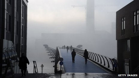 People walking through thick fog at the Millennium Bridge over the River Thames