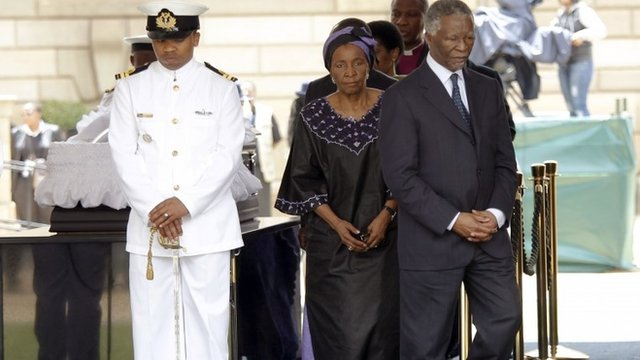 Former South African president Thabo Mbeki (R) walks on after paying his respects at the coffin of former South African President Nelson Mandela as he lies in state at the Union Buildings in Pretoria December 11