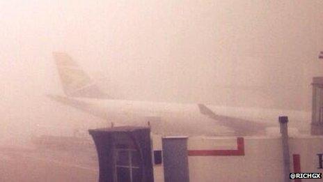 A plane seen through the fog at Heathrow