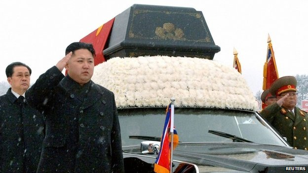 """North Korea""""s new leader Kim Jong Un (2nd L) salutes as he and his uncle Jang Song Thaek (L) accompany the hearse carrying the coffin of late North Korean leader Kim Jong Il during his funeral procession in Pyongyang in this file photo taken by Kyodo December 28, 2011."""