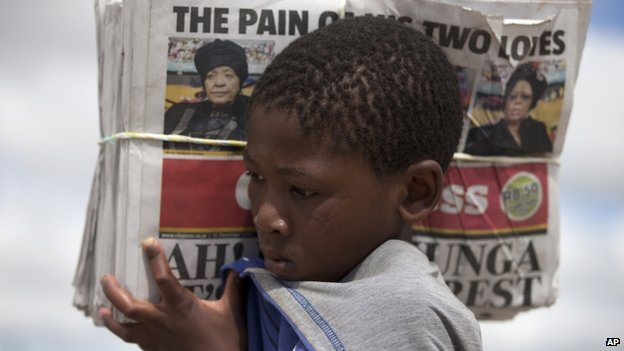 A boy carries newspapers in Nelson Mandela's home village of Qunu