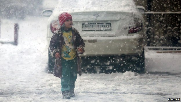 Child walks during snow fall in the Duma neighbourhood of Damascus (13 December 2013)