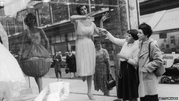 Circa 1950: Passers-by admire the unusual designs in a shop window