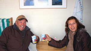 Roger and Sheila Widdup inside their hut with cups of tea