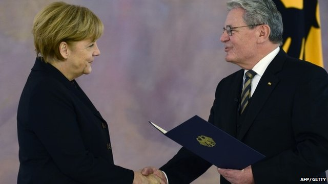 German President Joachim Gauck (R) hands over the certificate of appointment to German Chancellor Angela Merkel on December 17, 2013 at Bellevue Palace in Berlin