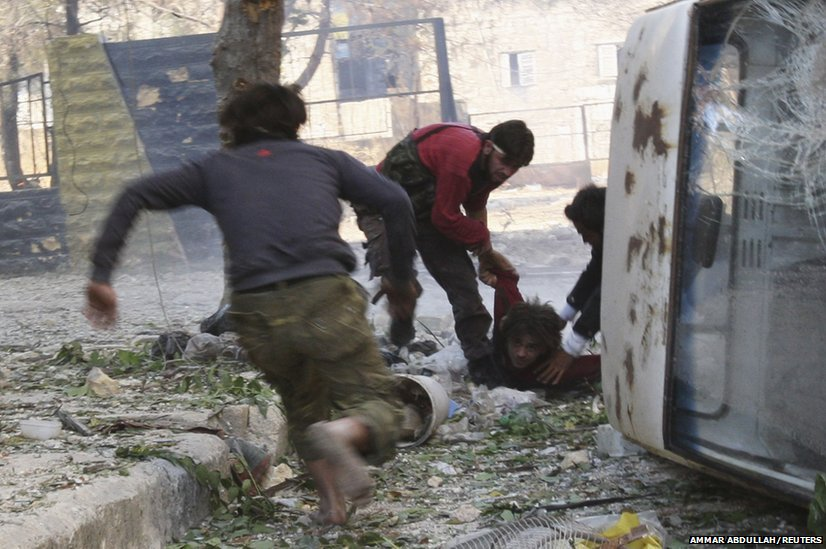 Free Syrian Army fighters rush to help their fellow fighter after he was shot by a sniper loyal to Syria's President Bashar al-Assad in Aleppo, 9 October 2013