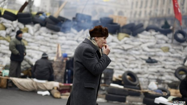 A pro-European integration protester eats a sandwich near a barricade during a rally in Independence Square in Kiev, December 16, 2013