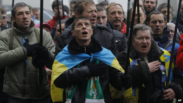 Pro-European Union activists sing the national anthem during a rally outside the office of the richest man of Ukraine Rinat Akhmetov during an anti-government protest in Kiev, Ukraine, Wednesday, Dec. 18, 2013.