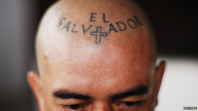 "A man with a tattoo on his forehead reading ""El Salvador"""