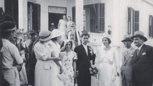black and white photo of a wedding party gathering in front of the house