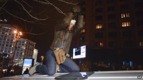 In this file photo from 25 November, 2013, Ukrainian journalist Tetyana Chornovol beats the roof of a police minivan with a stone during a pro-European Union rally in Kiev