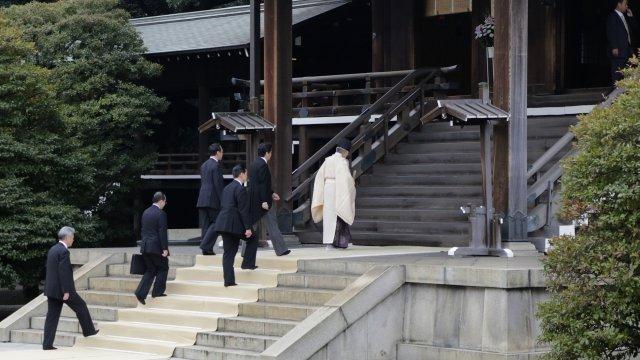Japanese PM Shinzo Abe follows priest up steps of shrine