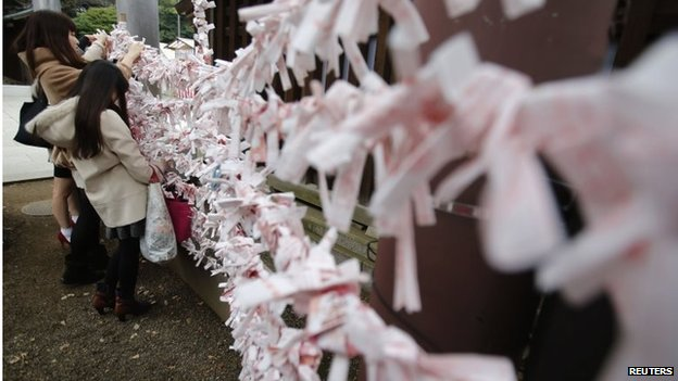 Visitors hang fortune blessing papers at Yasukuni Shrine in Tokyo December 26