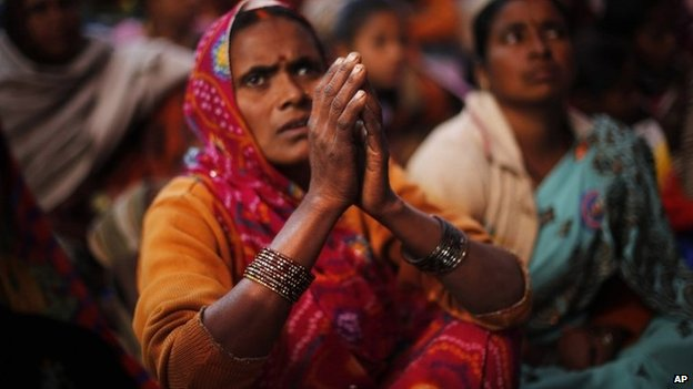 A Dalit woman listens to a speaker with folded hands during a protest on Human Rights Day near the Indian Parliament in Delhi, Tuesday, Dec 10, 2013