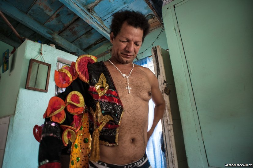 A cabaret performer dressing in his one-room home in Old Havana