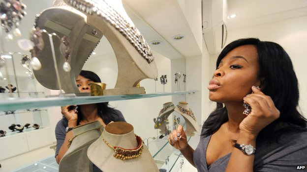A customer tries a fashion accessory displayed for sale at Temple Muse in Lagos on June 14, 2013.