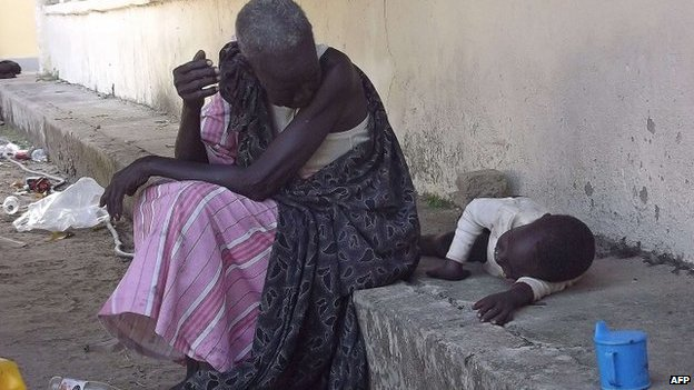 A South Sudanese woman sits with a child sits at the main hospital in Bor, after its recapture by government forces, 25 December