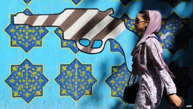Young woman and mural showing gun