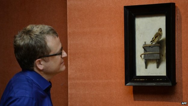 Man looking at The Goldfinch by Carel Fabritius