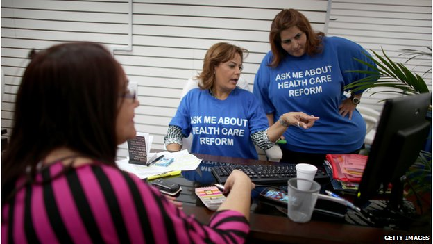 Ines Leyva talks to insurance agents with Sunshine Life and Health Advisors, as she looks to purchase an insurance policy under the Affordable Care Act in Hialeah, Florida (November 14, 2013)