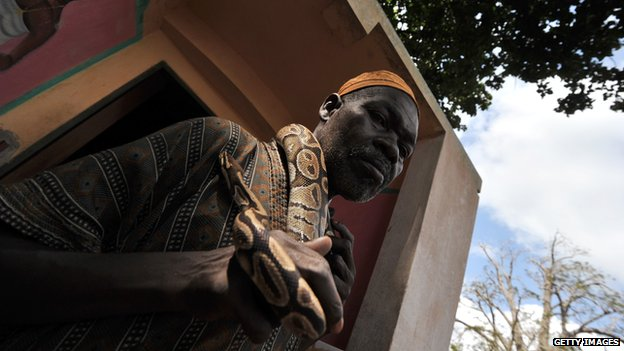 A Benin resident caretaker of the Temple of Pythons holds a python around his neck