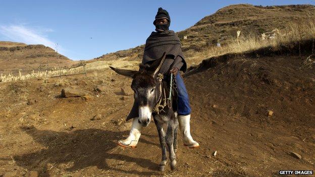 A young Basotho man rides his donkey