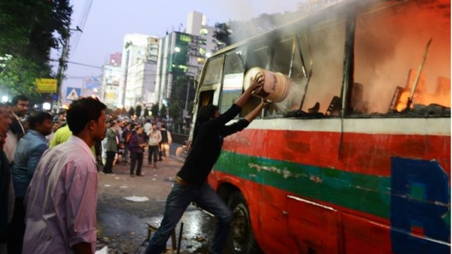 A Bangladeshi resident throws water onto a burning bus in Dhaka on January 2, 2014