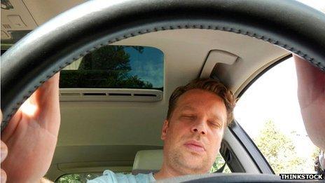 A man asleep at the wheel of a car