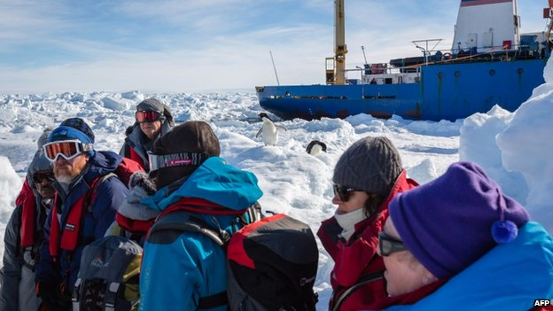 Penguins and passengers from the stranded Russian ship Akademik Shokalskiy wait for a helicopter from the nearby Chinese icebreaker Xue Long to pick them up after over a week of being trapped in the ice off Antarctica