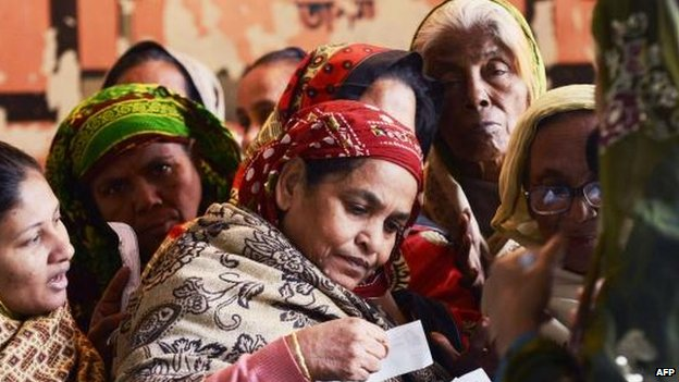 Voters check registration documents at a Dhaka polling station, 5 Jan