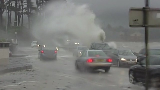 Waves crash over a road in Northern Ireland