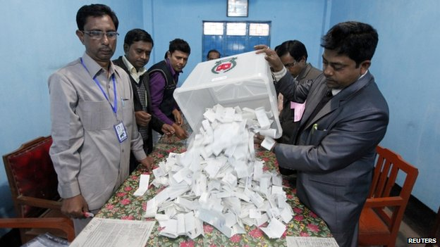 A polling officer pours ballot papers from a box onto a table to count during parliamentary elections in Dhaka January 5, 2014.