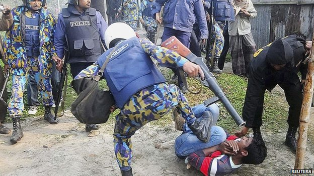 A police officer kicks a protester during a clash after protesters attacked and set fire to polling booths in Bogra January 5, 2014