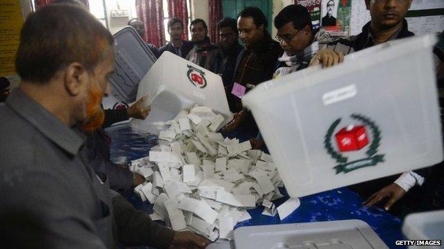Bangladeshi election officials open a ballot box to count votes