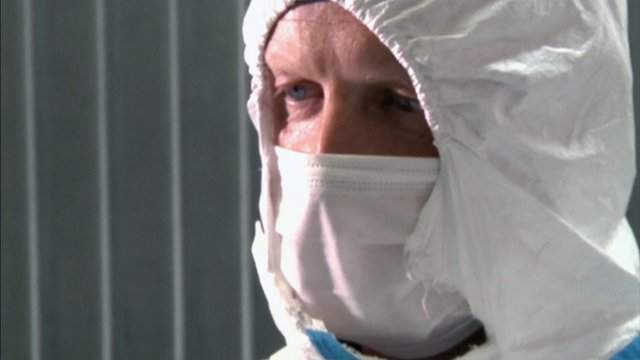 Man wearing forensics clothing and mask