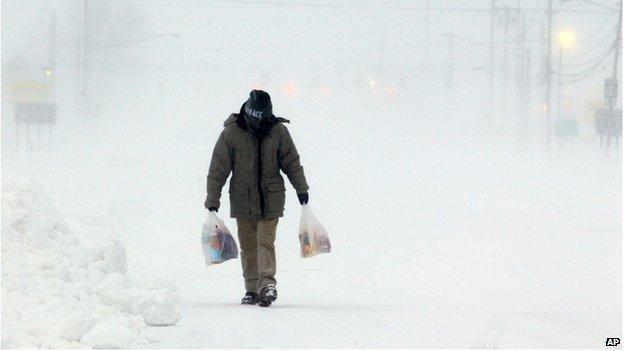 A man walks down a snow covered street in Hamburg, New York on 7 January 2014