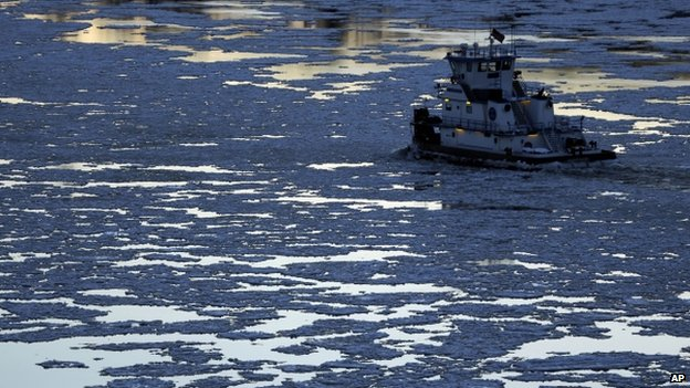 A tug boat navigates the frozen Mississippi River in St. Louis, Missouri