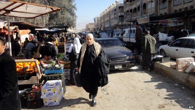 Iraqis shop at a market in Fallujah (8 January 2014)