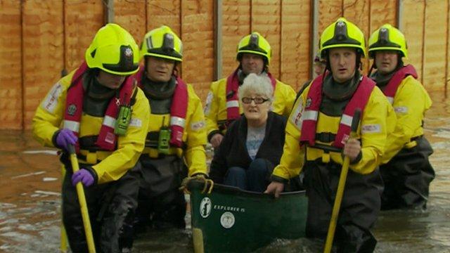 Elderly lady in canoe helped by rescue teams