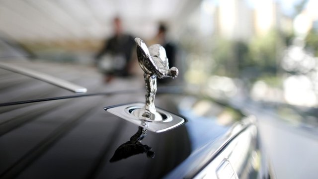 "A Rolls-Royce mascot known as the ""Spirit of Ecstasy"" stands on the front of a Rolls-Royce Ghost in a showroom in Singapore October 8, 2013"