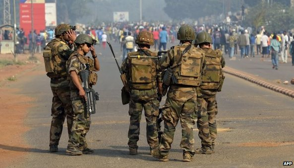 French troops stand guard as anti-Seleka protesters demonstrate following the resignation of the president in Bangui