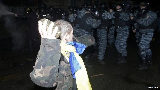 Opposition activist throwing a brick at riot police during a rally near a court in Kiev (10 January 2014)