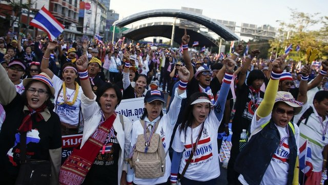 Anti-government protesters block the road at one of major intersections in central Bangkok