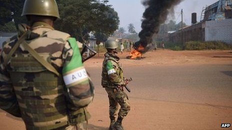 Congolese soldiers from the African-led International Support Mission to the Central African Republic (MISCA) stand guard in a street where people burnt tyres following the killing of a man by an ex-Seleka member, on 12 January 2014, in Bangui