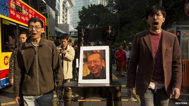 Pro-democracy protesters carry a seat with a posters of Chinese Nobel Peace Prize laureate Liu Xiaobo during a protest to urge for the release of jailed Liu and his wife Liu Xia in Hong Kong, 25 December 2013