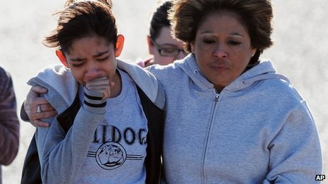 A student, left, is hugged after being united with families following a shooting at Berrendo Middle School, Roswell, New Mexico 14 Janury 2014