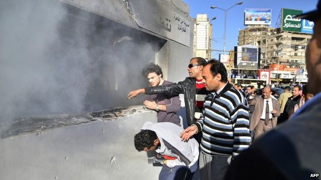 Egyptians gather outside a police station after it was set on fire